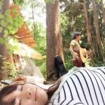 森でお昼寝しながら歌を聴く画像。